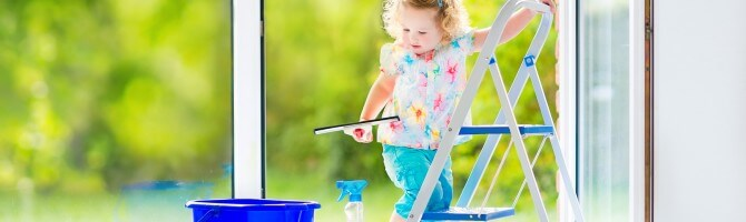 Little toddler girl washing a window with view garden