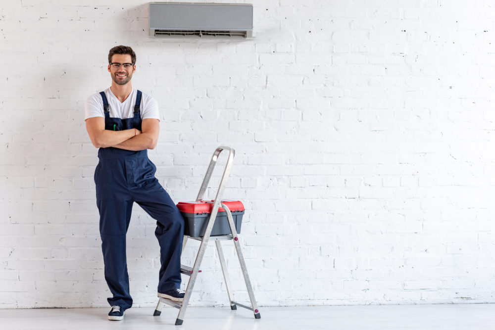 usmiechniety pracownik na tle bialej sciany z drabina